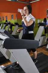 Young woman drinking water while working out