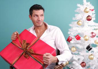 Unterm Weihnachtsbaum Mann packt Geschenk aus