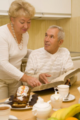 Elderly couple discuss a book during breakfast
