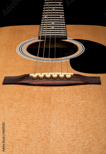 Close-up of acoustic guitar, focus on the bridge, on black backg