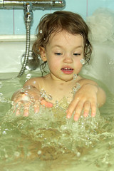 A little girl bathes.