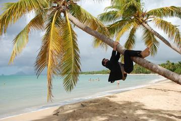 Plage des Antilles - Homme en costume grimpant à un cocotier