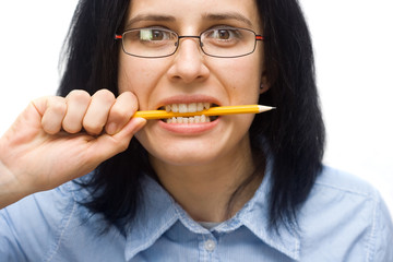 angry woman wearing glasses biting a pencil