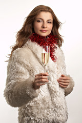 Young beautiful woman in white fur coat with glass of champagne