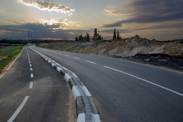 road near the city at sunset