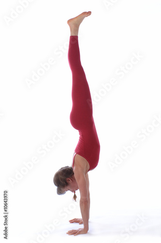 Woman in red leotard practices yoga in front of white background