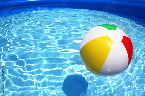 Leinwanddruck Bild Beach ball floating on pool