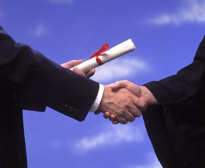 presentation of a diploma and a handshake at graduation
