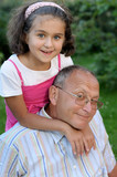 Smiling grandfathe and granddaughter outdoors poster