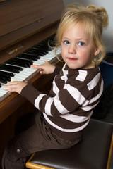 Kind musiziert auf einem Klavier
