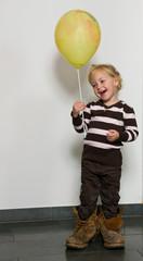 Kind in großen Schuhen und Luftballon hat Spass