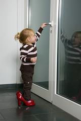 Kind mit großen Schuhen öffnet eine Türe