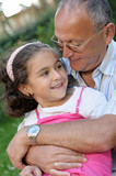 Grandfather and granddaughter outdoors poster