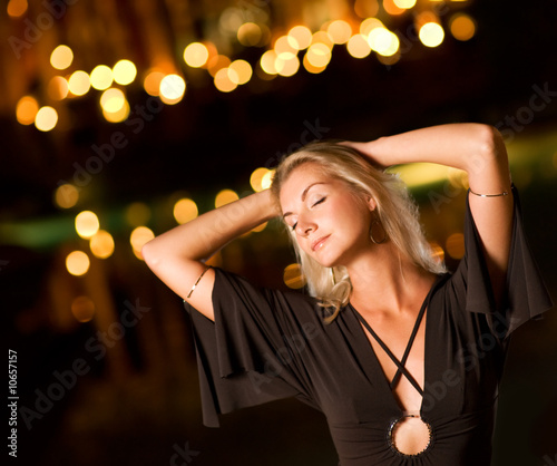 Beautiful young woman dancing late at night