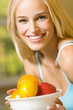 Portrait of young happy smiling woman with plate of fruits