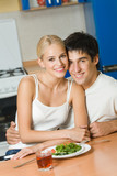 Young happy couple with vegetarian salad at kitchen