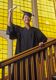 a university graduate holds her diploma overhead poster