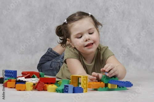 4 years old girl playing with toys Poster