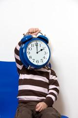 Kind mit Uhr als  Symbol Sommerzeit Umstellung