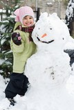 Cute little girl playing in winter backyard with a huge snowman poster