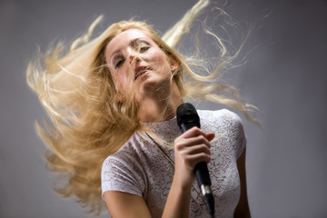 beautiful blond young woman singing into a microphone