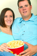 Young Caucasian Couple Watching Movie Eating Popcorn