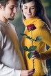 Young happy smiling couple with rose on romantic date
