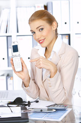 Beautiful business woman showing her mobile phone and smiling