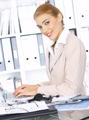Beautiful business woman working on laptop in office, smiling