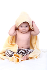 bright portrait of adorable baby wrapped in towel