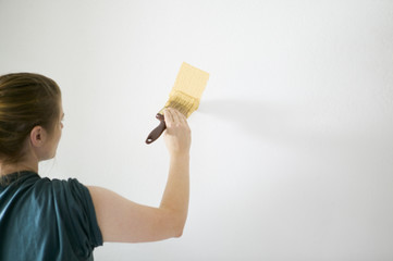 Woman painting white wall with bright yellow paint