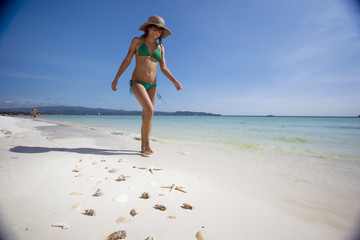 young girl walking on a tropical beach with seashells