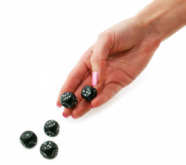 Female hand rolling black dice