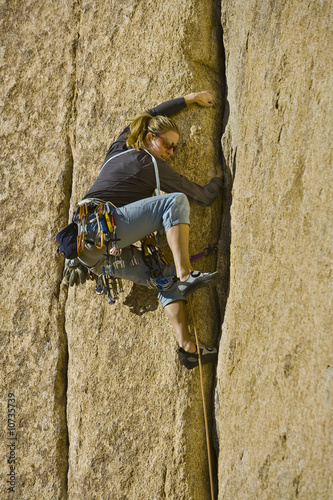 Female climber clinging to a cliff.