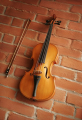 Violin & bow over red brick wall
