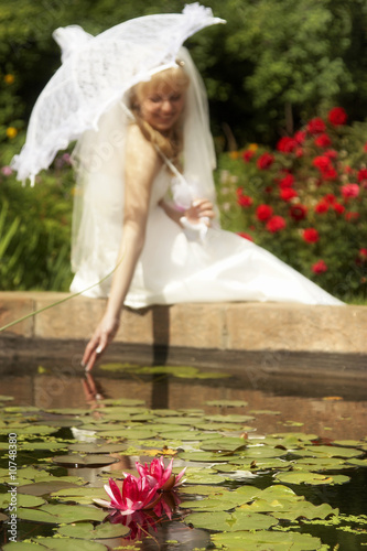 Bride with lace umbrella in the garden