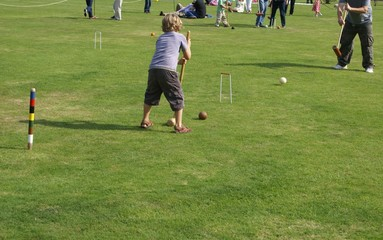 young child playing croquet