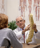 a chiropractor showing a patient a model of spine poster