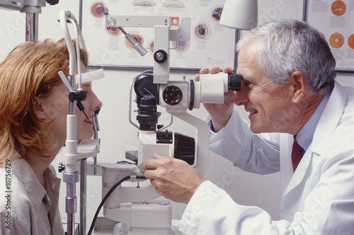 optometrist with patient, giving an eye examination - 10756729