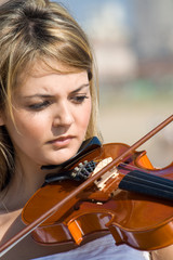 young blond woman play violin on beach