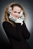 curly young woman in furs earphone and mitten poster