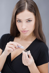 Woman holding contact lens. Focus on lenses container