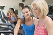 Personal Trainer Showing Woman How To Use Treadmill