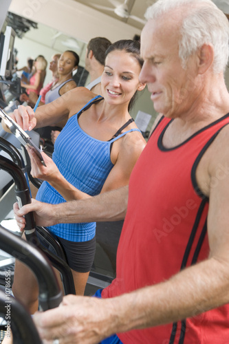 Personal Trainer Instructing Man On Treadmill