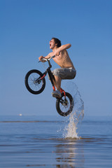 Teen jumping with the bike in water
