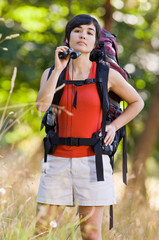 Curious woman with backpack and binoculars