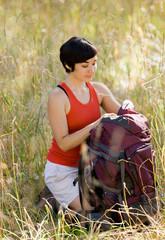 Woman opening backpack in field