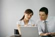 Homme et femme d'affaires au bureau devant ordinateur