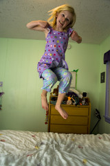 Angry girl jumping on a bed