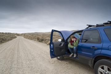 Teenage girl with a broken car